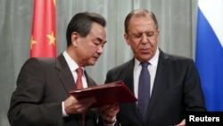 2015年4月7日俄罗斯外交部长谢尔盖·拉夫罗夫(右)在莫斯科与中国外交部部长王毅交换文件