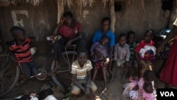 FILE - South Sudanese refugees who fled fighting between government and rebel forces wait in the shade of a dilapidated church near Aba, South Sudan, to be taken to a nearby refugee camp on Dec. 19, 2017.