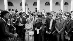 President John Kennedy speaks to Peace Corps volunteers in the White House Rose Garden August 28, 1961