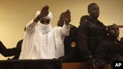 FILE - Chad's former dictator Hissene Habre raises his hands after sentencing during court proceedings in Dakar, Senegal, May 30, 2016.