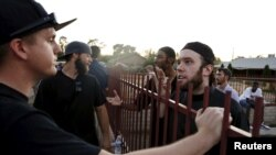 "Members of the Islamic Community Center, including Ilyas Wadood, right, talk with people attending the ""Freedom of Speech Rally Round II"" outside the center in Phoenix, Arizona, May 29, 2015."