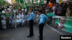 Policemen stand guard near supporters of the Pakistan Muslim League - Nawaz (PML-N) party during an election campaign rally in Islamabad, May 5, 2013.