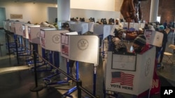 Voters cast their ballots at privacy booths during early voting at the Brooklyn Museum in New York, Oct. 27, 2020.