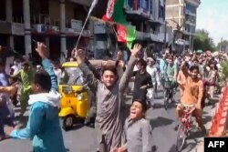 This screengrab taken from video from Pajhwok Afghan News shows Afghan people protesting over the reported removal of Afghan flags replaced with Taliban flags after the Taliban's military takeover of Afghanistan, in Jalalabad on August 18, 2021. …