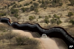 FILE - A Customs and Border Control agent patrols on the U.S. side of a razor-wire-covered border wall along Mexico east of Nogales, Ariz., March 2, 2019.