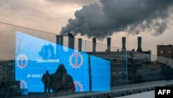 FILE - Pedestrians and an electronic screen displaying COVID-19 prevention advice is reflected in a glass wall as smog billows from a factory in Moscow, Dec. 3, 2020.