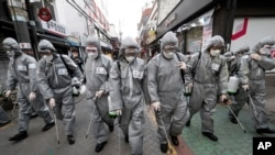 Army soldiers wearing protective suits spray disinfectant as a precaution against the new coronavirus at a shopping street in Seoul, South Korea, Wednesday, March 4, 2020. The coronavirus epidemic shifted increasingly westward toward the Middle East…