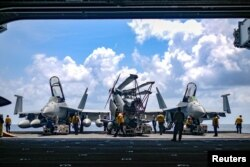 FILE - U.S. Navy sailors move aircraft from an elevator into the hangar bay of aircraft carrier USS Theodore Roosevelt in South China Sea, Apr. 8, 2018. (US Navy/Mass Communication Specialist Seaman Michael Hogan/Handout via Reuters)