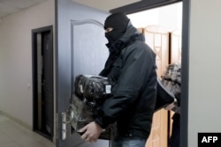 A policeman leaves the BAJ office after a raid in Minsk, on Feb. 16, 2021. Police in Belarus also raided the homes and offices of 25 journalists, rights defenders and trade union members.