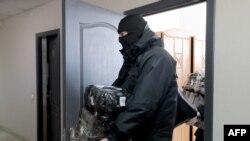 Сотрудник спецназа после проведения обыска в помещении Белорусской ассоциации журналистов (архивное фото)