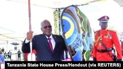 Le président John Magufuli, tient une lance et un bouclier reçus des chefs traditionnels après avoir prêté serment pour son second mandat au stade Jamhuri de Dodoma, en Tanzanie, le 5 novembre 2020.