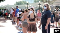 FILE - Guests wearing protective masks wait outside the Magic Kingdom theme park at Walt Disney World on the first day of reopening, in Orlando, Florida, on July 11, 2020.