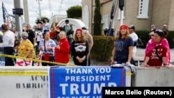 Para pendukung mantan presiden Donald Trump menunggu rombongan Trump di West Palm Beach, Florida, 20 Januari 2021. (Foto: Marco Bello/Reuters)