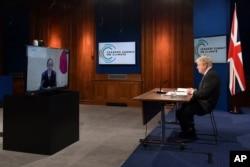 스가 요시히데 일본 총리가 22일 화상으로 열린 기후정상회의에서 연설하는 모습을 보리스 존슨 영국 총리가 런던에서 보고 있다.