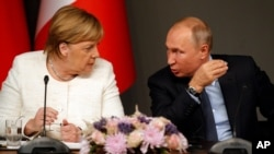 German Chancellor Angela Merkel, left, listens to Russian President Vladimir Putin as they attend a news conference following a summit on Syria, in Istanbul, Oct. 27, 2018.