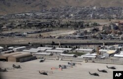 Kabul Military Airport where helicopters are parked are seen through a window of a commercial airplane, July 7, 2021.
