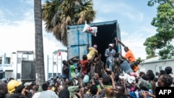 """A man throws a bag of rice into a crowd of earthquake victims gathered for the distribution of food and water at the """"4 Chemins"""" crossroads in Les Cayes, Haiti, Aug. 20, 2021."""