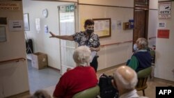 Home manager Theresa Swart, center, explains to elderly guests of the retirement home how the Pfizer vaccine works during a vaccination run near Klerksdorp, South Africa on May 19, 2021.
