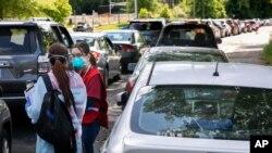 Voluntarios en Annandale, Virginia, se colocan entre cientos de automóviles para registrar a las personas que se alinean para las pruebas de COVID-19, el sábado 23 de mayo de 2020.