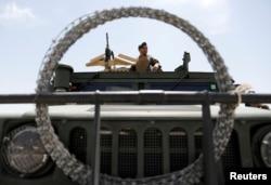 An Afghan security forces member keeps watch as he sits in an army vehicle in Bagram U.S. air base, after American troops vacated it, in Parwan province, Afghanistan, July 5, 2021.