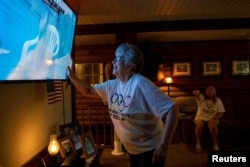 Karen Armstrong reaches to touch a screen displaying her grandson, U.S. swimmer Hunter Armstrong, during the 2020 Olympic Games in Tokyo, while his family watches from home in Dover, Ohio, July 25, 2021.