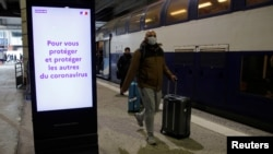 A man wearing a protective face mask walks past an announcement for travelers to protect themselves and others from the coronavirus, at Montparnasse train station in Paris, France, March 13, 2020.