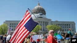 People gather outside the Missouri Capitol to protest stay-at-home orders put into place due to the COVID-19 outbreak, April 21, 2020, in Jefferson City, Missouri.