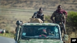 FILE - Ethiopian government soldiers ride in the back of a truck on a road near Agula, north of Mekele, in the Tigray region of northern Ethiopia, May 8, 2021.