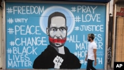 A man walks past a mural depicting George Floyd during a protest over the death of Floyd Sunday, May 31, 2020, in Los Angeles. Floyd died in Minneapolis on May 25 after he was pinned at the neck by a police officer. . (AP Photo/Ringo H.W. Chiu)