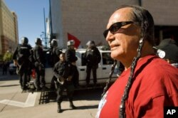 FILE - In this Saturday, Oct. 6, 2007 file photo, American Indian Movement activist Russell Means looks at the start of the Columbus Day Parade in Denver, Colo.