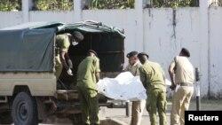 Pasukan keamanan Tanzania mengeluarkan mayat seorang penyerang yang memegang senapan serbu, di luar kedutaan Perancis di daerah Salenda, Dar es Salaam, Tanzania, 25 Agustus 2021. (Foto: Reuters)
