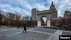 People walk around Washington square park as the coronavirus disease (COVID-19) outbreak continues in New York, U.S., March 22, 2020.