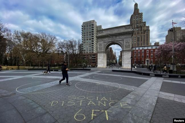Gente camina alrededor del parque Washington Square en Nueva York el 22 de marzo de 2020, mientras la pandemia de COVID-19 continúa afectando la ciudad.