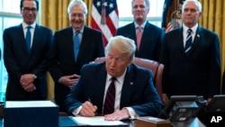 Presidenti Donald Trump në momentin e nënshkrimit në Zyrën Ovale të paketës ligjore për asistencën ekonomike (27 mars 2020)