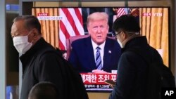 Masked people walk in front of a TV screen showing a live broadcast of U.S. President Donald Trump's speech at the Seoul Railway Station in Seoul, South Korea, March 12, 2020.