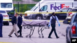 A body is taken from the scene where multiple people were shot at a FedEx Ground facility in Indianapolis, April 16, 2021.