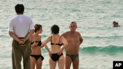 A fully clothed man enjoys the view as he walks along the beach, as two women talk to a man on the Umm Suqaim public beach in Dubai, United Arab Emirates, Monday, July 16, 2008. Authorities in the Persian Gulf tourist haven of Dubai are cracking…
