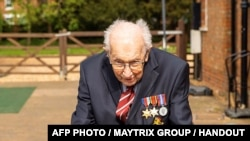 A handout photo taken in April 2020, and released by the Maytrix Group in London on April 14, 2020, shows World War Two (WWII) veteran 99-year-old Captain Tom Moore walking in his garden in Marston Moretaine, north of London, to raise money for Britain's