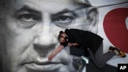 Seorang wanita ikut melakukan protes terhadap Perdana Menteri Israel Benjamin Netanyahu, yang terlihat di poster, di Tel Aviv, Israel, 19 April 2020. (Foto: AP)