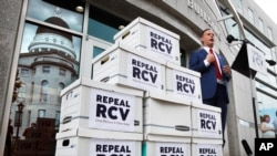Jason Savage, executive director of the Maine GOP, speaks about efforts to repeal ranked-choice voting while standing next to boxes containing signed petitions near the State House, Monday, June 15, 2020, in Augusta, Maine. The state Republican…