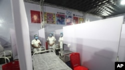 FILE - Nurses from the Tata Memorial Hospital stand inside a temporary facility created to screen cancer patients for COVID-19 in Mumbai, July 30, 2020.