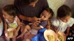 Una pequeña es alimentada por su madre junto a otras dos niñas cuando son asistidas por el miembros del Programa Mundial de Alimento (PMA), en Orcuina, Honduras. [Foto de archivo]