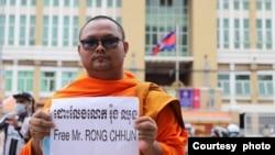 """ຄູບາ Bor Bet ທີ່ເປັນນັກເຄື່ອນໄຫວຖືປ້າຍທີ່ຂຽນວ່າ 'Free Mr. Rong Chhun' ຊຶ່ງແປວ່າ """"ຈົ່ງປ່ອຍຕົວທ່ານຣອງ ຈະຮຸນ) ຢູ່ຕໍ່ໜ້າສານໃນນະຄອນພະນົມເປັນ ໃນເດືອນສິງຫາ 2020. (ພາບໂດຍຄູບາ Bor Bet)"""