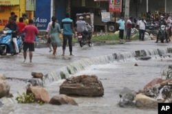Warga berjalan melewati kawasan yang tergenang banjir setelah hujan lebat melanda Hyderabad, India, India, Rabu, 14 Oktober 2020.