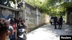 Periodistas se reúnen junto a los agentes de policía que hacen guardia cerca de la residencia privada del presidente de Haití, Jovenel Moise, después de que hombres armados lo mataran a tiros con rifles de asalto, Puerto Príncipe, el 7 de julio de 2021.