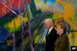 FILE - German Chancellor Angela Merkel, right, walks with then-U.S. Vice President Joe Biden for a meeting at the chancellery in Berlin, Germany, Feb. 1, 2013.
