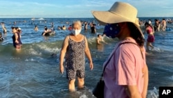 Women wearing face masks stand on a beach in Vung Tau city, Vietnam, Sunday, July 26, 2020. Vietnam on Sunday reimposed restrictions in one of its most popular beach destinations after a second person tested positive for the virus, the first locally…