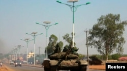 FILE - A military tank patrols along one of the main roads in the South Sudanese capital Juba, Dec. 16, 2013. Three deadly road attacks occurred in South Sudan this week, leaving 10 people dead.