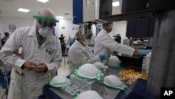 Seorang petugas memeriksa masker yang baru diproduksi di sebuah pabrik di Mexico City, 21 Mei 2020.