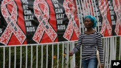FILE - In this Friday, Dec. 1, 2017 file photo, a woman walks past a World AIDS Day banner in Johannesburg, South Africa. In 2019 fewer people in many parts of sub-Saharan Africa are dying of AIDS as treatment becomes more widely available, yet some…